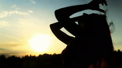 A silhouette of a woman  on a sunset touching her hair - stock footage