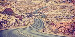 Vintage toned curved desert highway, travel adventure concept, USA. Stock Photos