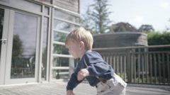 4K Happy little boy with lots of energy playing on his own outdoors Stock Footage
