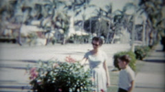 1959: Mom and son of tree lined street as old classic car passes. Stock Footage