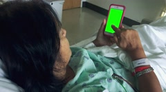 Woman scrolling through smartphone while laying down in hospital bed Stock Footage
