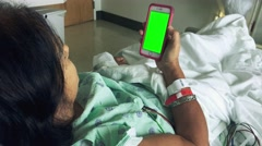 Woman in hospital bed looking at something in her mobile device Stock Footage