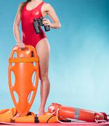 Stock Photo of Lifeguard with rescue buoy supervising.