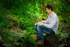 Young handsome man using laptop with great internet connectivity in the jungle Stock Photos