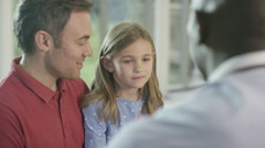 4K Friendly doctor talking to father and child patient in office. - stock footage