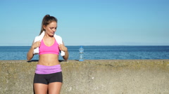 Stock Video Footage of Woman doing sports outdoors by seaside drinking water 4K