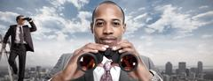 African-American businessman with binoculars. Stock Photos