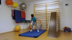 A young man using a hula hoop in her training in the gym Stock Footage