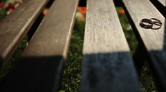 Two Gold Wedding Ring in infinity sign, lying on a wooden bench on a green young Stock Footage