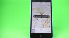 A smartphone with the Uber app showing the map of Kuala Lumpur Stock Footage