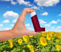 Asthma inhaler in hand. - stock photo