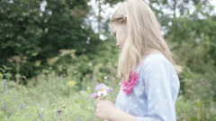 4K Portrait of pretty smiling little girl picking wildflowers outdoors - stock footage