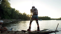 Wakeboarder in protection shoes start action on the board Stock Footage