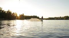 A young man riding a wakeboard at sunset Stock Footage