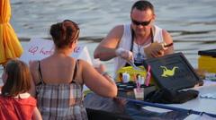 Man making a hotdog on the riverside in Prague - stock footage