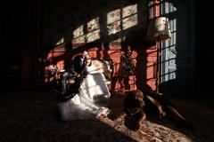 Beautiful bride and groom embracing and kissing in old vintage room - stock photo