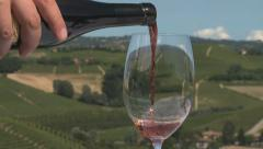 Pouring red wine into a glass with vineyards in the background in Italy - stock footage