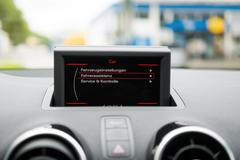 Display at a dashboard in a car with blurred background. Stock Photos