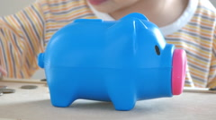 Little girl putting money in piggy bank Stock Footage