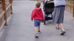 Stock Video Footage of Mother and toddler pushing a stroller gimbal shot
