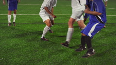 A soccer player dribbles down the field during a game at night Stock Footage