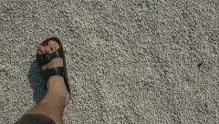 Adult male in slippers walking on white pebbles - stock footage