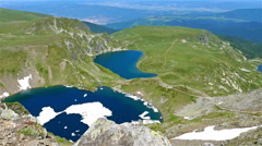 Breathtaking view with mountains, lakes and green field Stock Footage