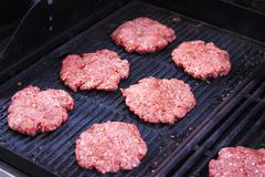 Grilling raw hamburger beefs - stock photo