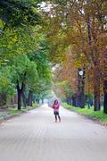 little girl with umbrella on street autumn season - stock photo