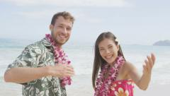 Hawaii beach couple saying welcome and come here showing hand gesture waving Stock Footage