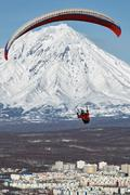 Paraglider flying over city on background of active volcano Stock Photos