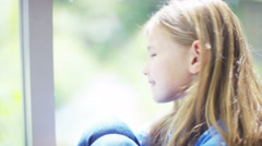 4K Portrait of pretty smiling little girl sitting by a window. Stock Footage