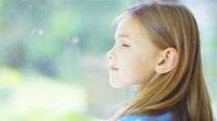 4K Portrait of pretty smiling little girl sitting by a window. Stock Footage
