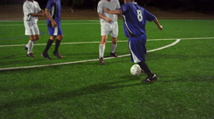 Soccer players pass the ball down the field at night and make a goal Stock Footage