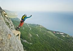 base-jumper jumps from the cliff - stock photo