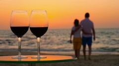 Couple admiring the sunset. In the foreground is the glasses with red wine on th Stock Footage