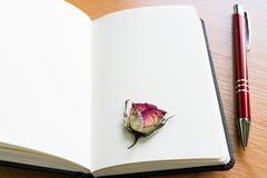 Open Notebook With Dry Rose On Wooden Table With Copy Space - stock photo