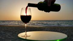 Man pouring red wine into a glass at sunset. Stock Footage