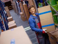 Porter carrying boxes in a warehouse - stock photo