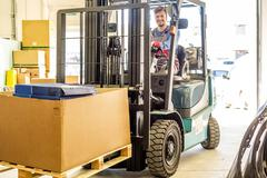 Man driving forklift truck on a warehouse Stock Photos