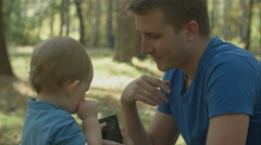 Father helps crying son to use cell phone in park Stock Footage