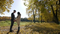 Boy and girl walk on autumn alley Stock Footage