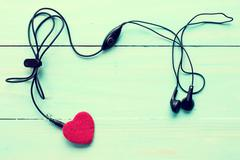 Stock Photo of Earphones and heart on wooden background