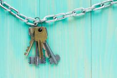 Keys hanging on blue wooden background - stock photo