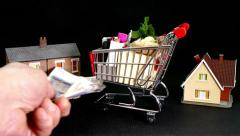 Full model shopping trolley pushed between two model houses, then sterling added Stock Footage