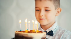 Little boy blowing out candles on birthday cake - stock footage