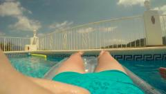 Woman floating in pool on inflatable lilo Stock Footage