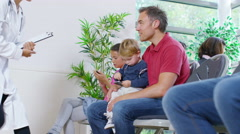 4K Man with cute young son talking to female doctor in medical waiting room - stock footage