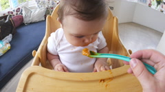 Point Of View Shot Of Baby Being Fed In High Chair Stock Footage