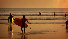 Tourists wading out of the ocean at sunset, after a long day of surfing - stock footage